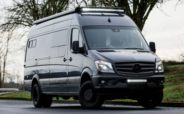 Deep dark grey Mercedes Sprinter van with roof top fog lights on road