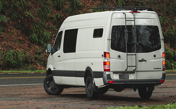 Ecru colored Mercedes Sprinter van with roof rack and rear ladder parked